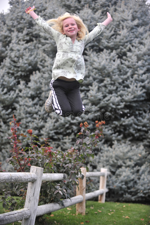 Young girl jumping from a fence stock image