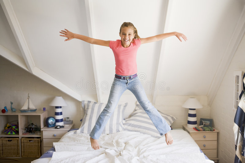 Download Young Girl Jumping On Her Bed Stock Photo - Image: 6440540