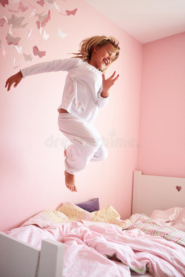 Download Young Girl Jumping On Her Bed Stock Photo - Image of bedroom, child: 33775550