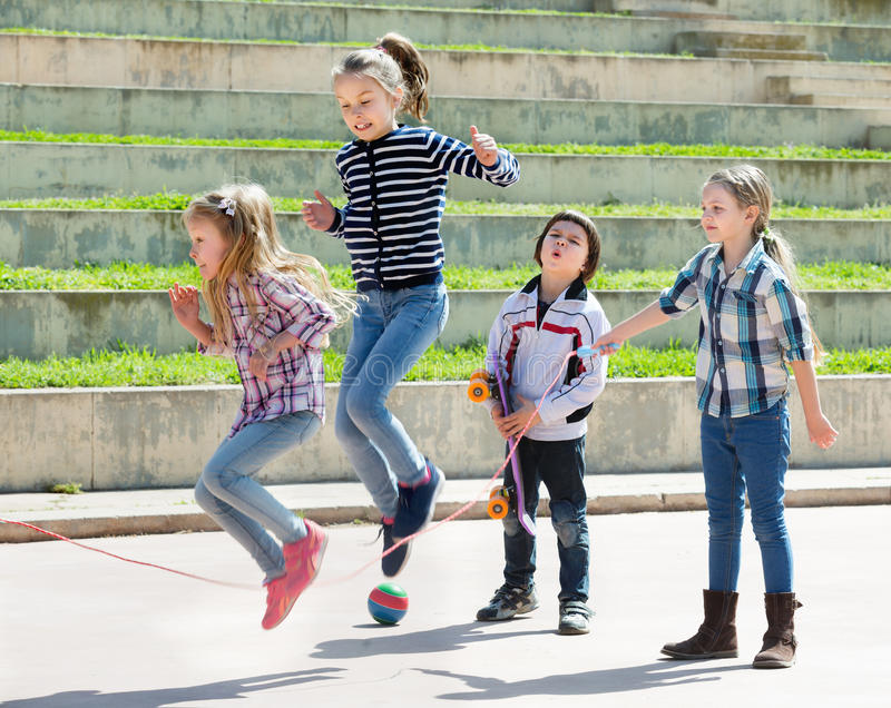 Young girl jumping while jump rope game. With friends outdoor royalty free stock photography