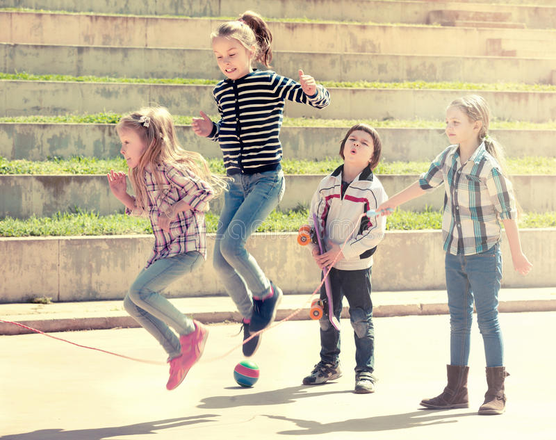 Young girl jumping while jump rope game. With friends outdoor stock photography