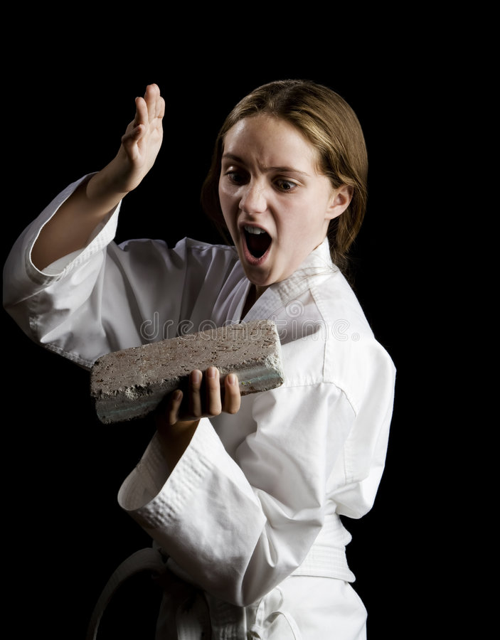 Young girl karate chopping a brick. On black background stock images