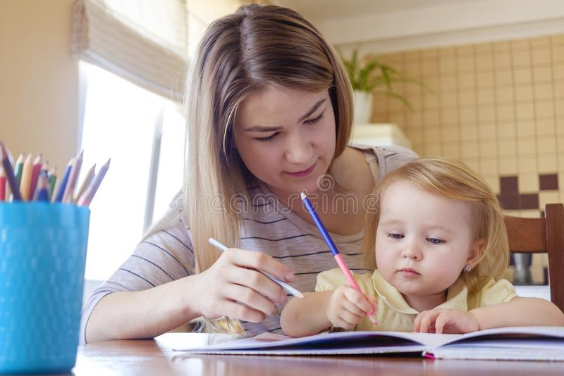 Young girl kid drawing with her sister. Young girl kid drawing with her elder sister or mother using crayons, sitting at the table together. Low angle front stock images