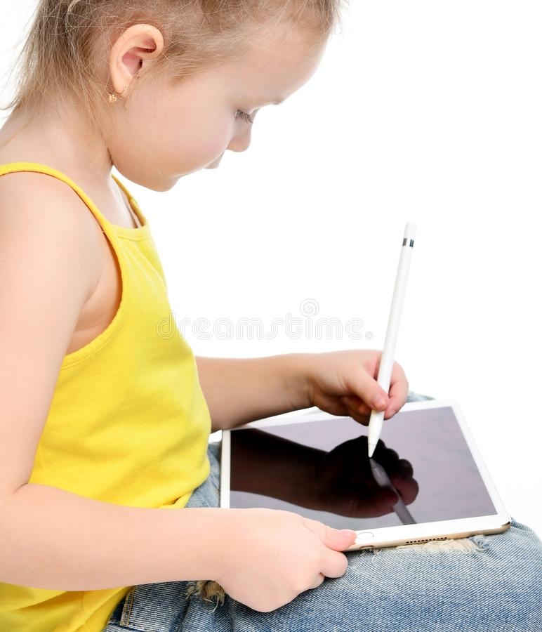Young girl kid sitting reading learning drawing on digital tablet touch screen pad with pencil royalty free stock images