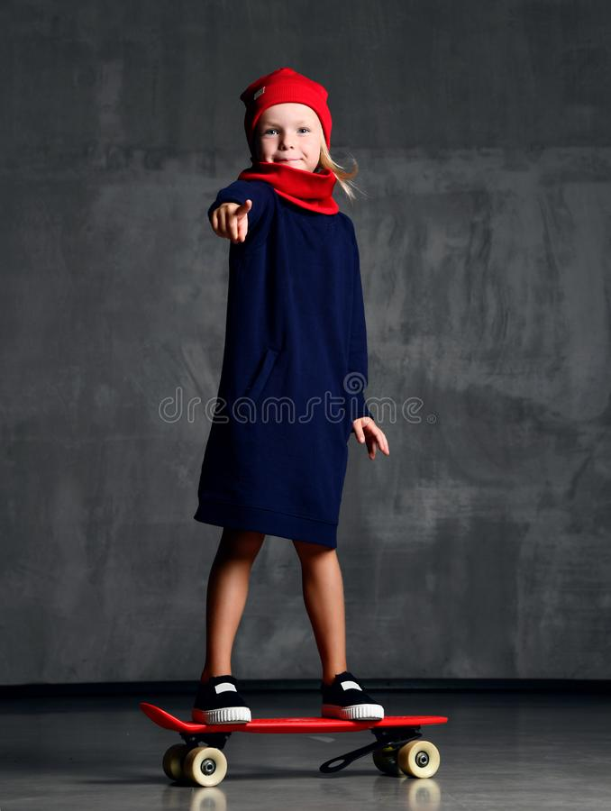 Young girl kid standing on skateboard in blue coat and red scarf and har pointing finger royalty free stock photo