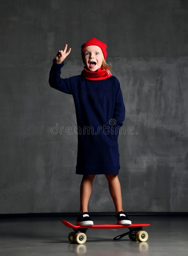 Young girl kid standing on skateboard in blue coat and red scarf and har showing peace sign screaming royalty free stock images