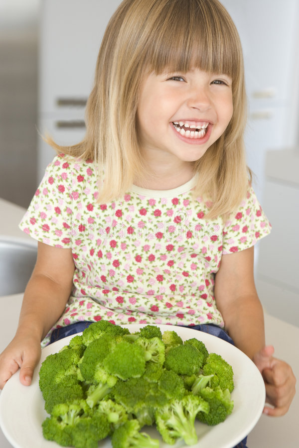 Young girl in kitchen eating broccoli smiling stock image