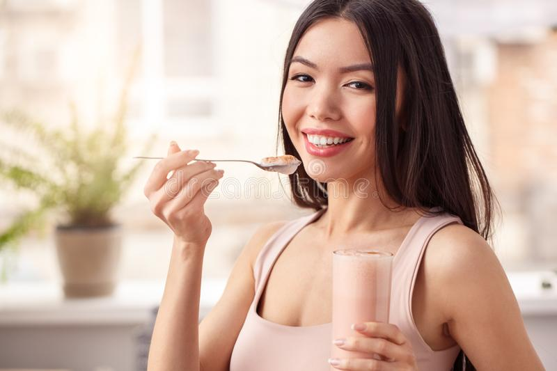 Young girl at kitchen healthy lifestyle standing eating smoothie from glass looking camera happy royalty free stock images