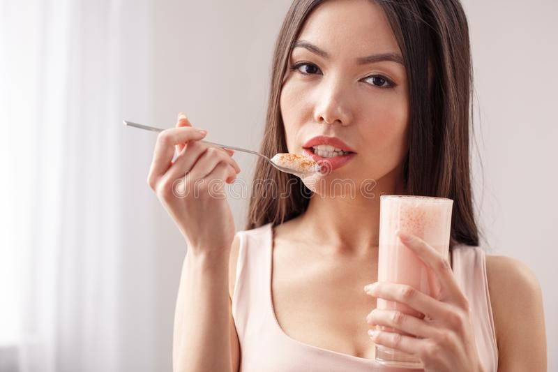 Young girl at kitchen healthy lifestyle standing holding glass eating smoothie looking camera close-up stock image