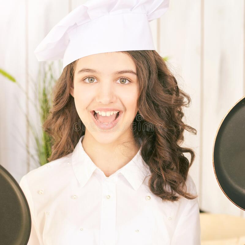 Young girl at kitchen. Little cook chef. Cute female portrait. Baker smile professional.  stock images