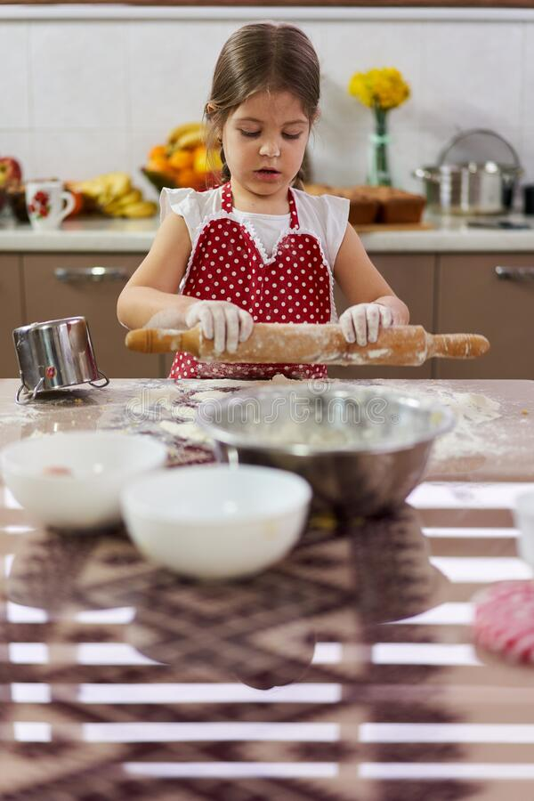 Young girl kneading dough stock images