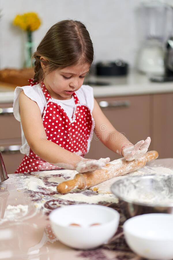 Young girl kneading dough stock photography
