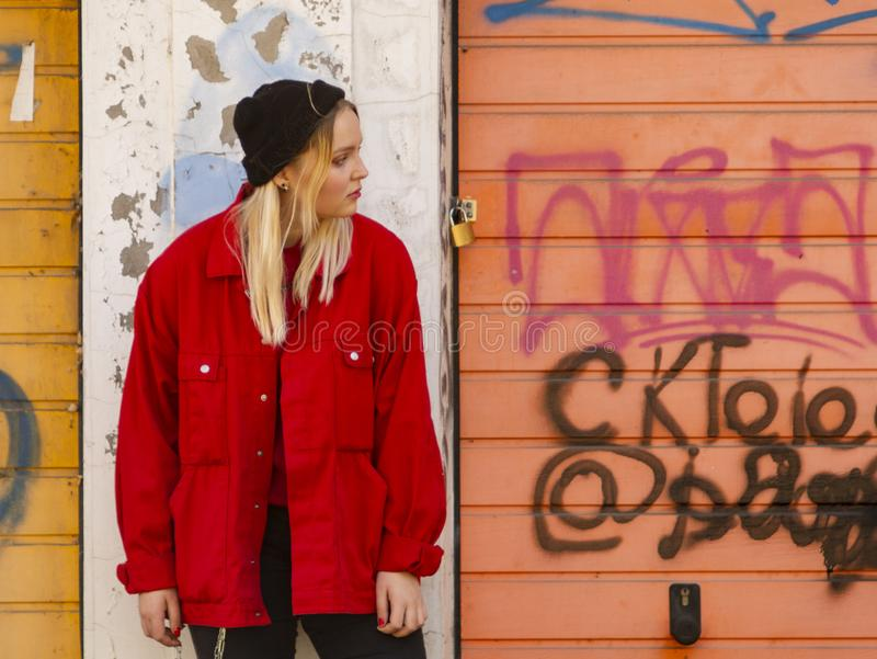A young girl in a knitted hat and a red jacket stands against the painted wall of a garage stock photography