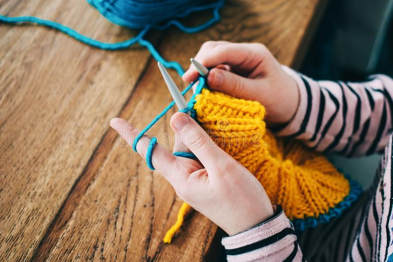 Young girl knitting a circle scarf with yellow and blue coloured. Yarn. Sitting at the wooden table, close up of the knitting needles royalty free stock photography