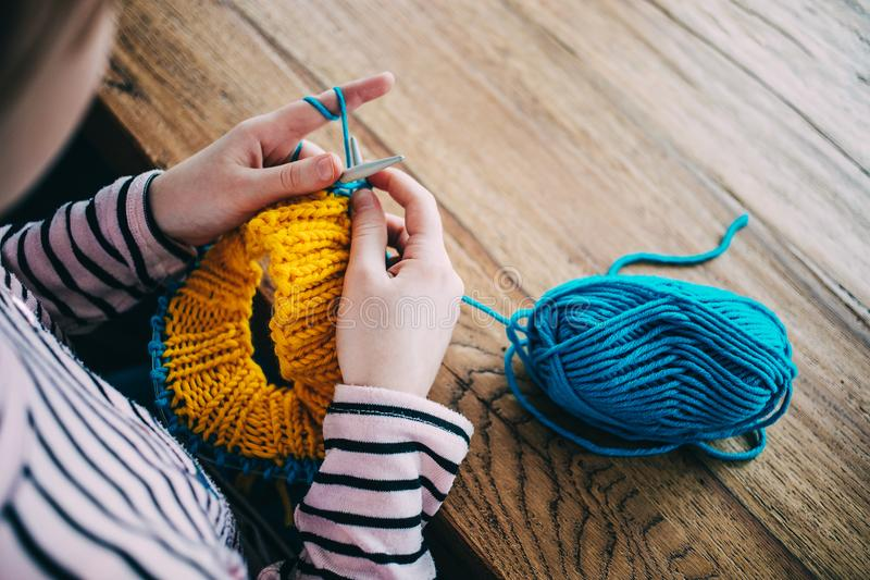 Young girl knitting a circle scarf with yellow and blue coloured. Yarn. Sitting at the wooden table, close up of the knitting needles stock photography