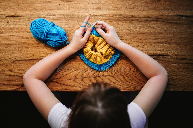 Young girl knitting a circle scarf with yellow and blue coloured. Yarn. Sitting at the wooden table, view from above stock image