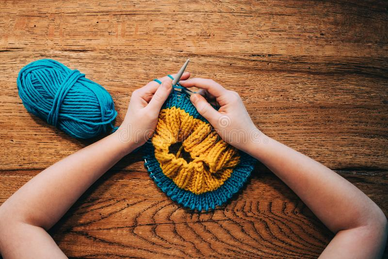 Young girl knitting a circle scarf with yellow and blue coloured. Yarn. Sitting at the wooden table, view from above, close up stock photography