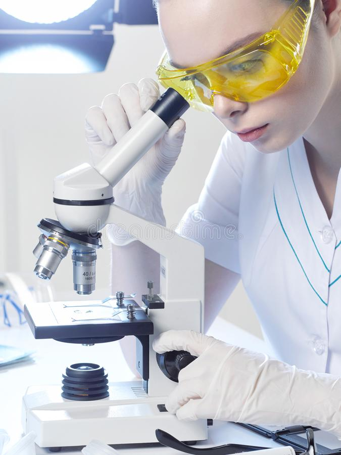 Young girl lab assistant looks into a microscope in a medical la. Young girl lab assistant or assistant doctor, in yellow goggles looks into a microscope in a stock photography