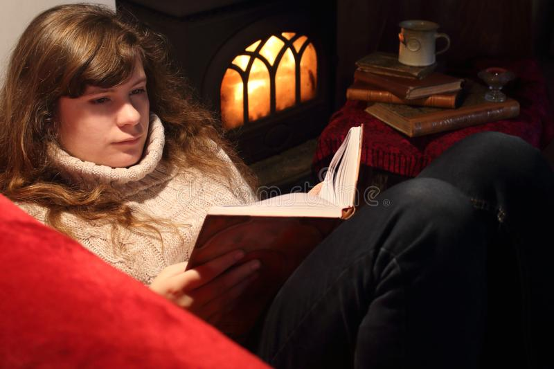 Young girl lady, woman sitting on sofa near wood stove with fire and her long brown hair lie on sweater and reading book stock image