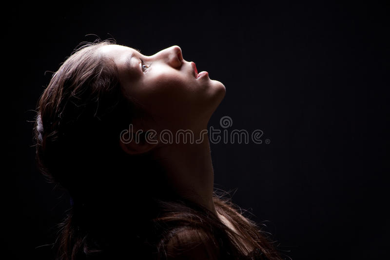Young girl lasting up to light on black. Close up portrait of charming young girl lasting up to light on black background royalty free stock photography