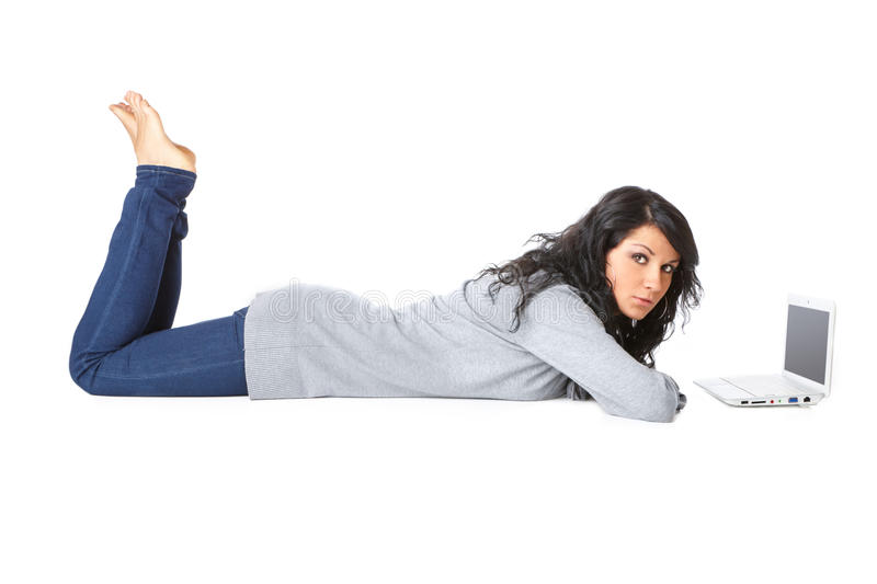 Young girl laying on the floor using a laptop. Portrait of beautiful young girl laying on the floor using a laptop over white background. Isolated stock photo