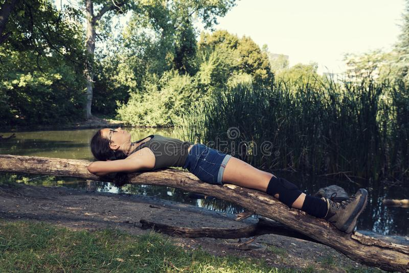 Young girl laying on a log in a park Summer time stock photos