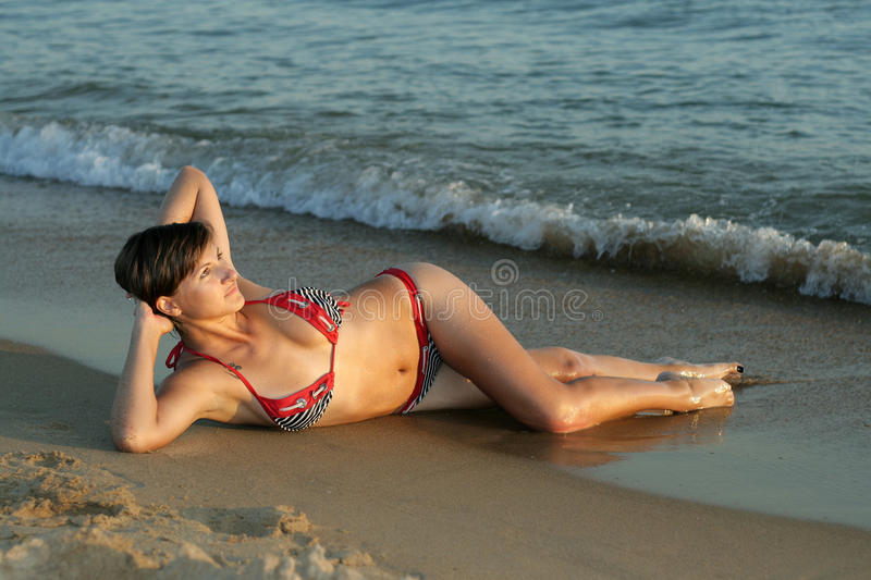 Young Girl Lays On The Beach Looking Afar Royalty Free ...
