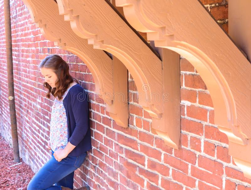 Girl Leaning Against Red Brick Wall royalty free stock photography