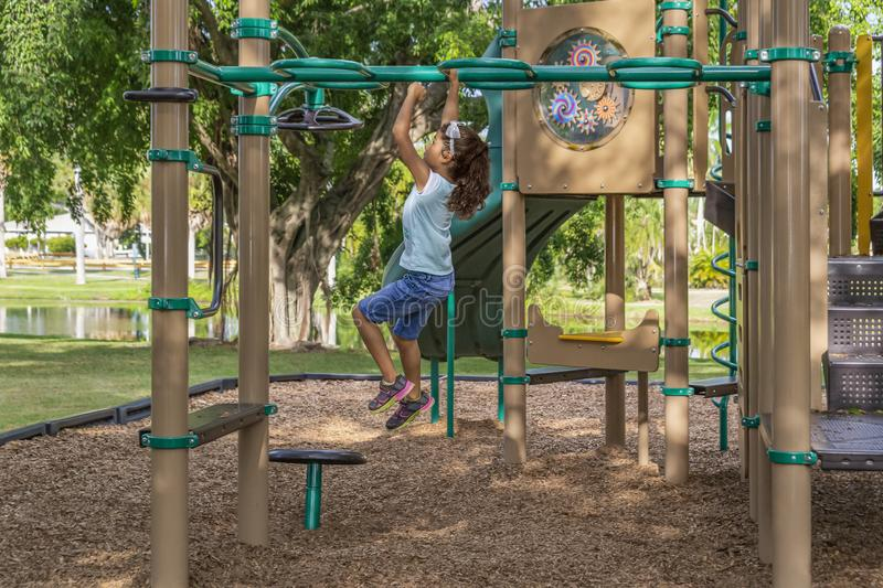The young girl leaps across the bars one hand at a time at the outdoor jungle gym stock photos
