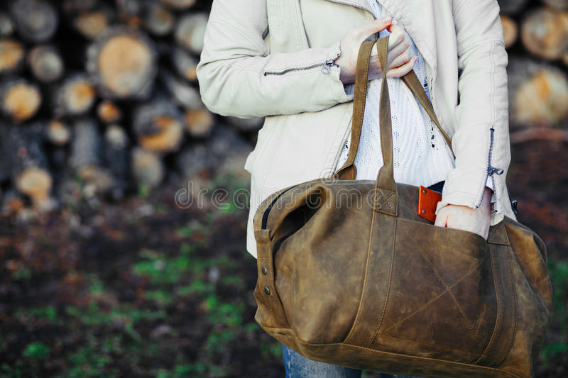 The young girl with a leather bag at a wall from logs. royalty free stock photos