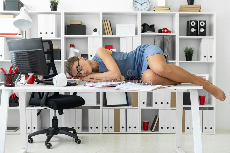 Young girl lies with closed eyes on documents on desk in office. stock photography