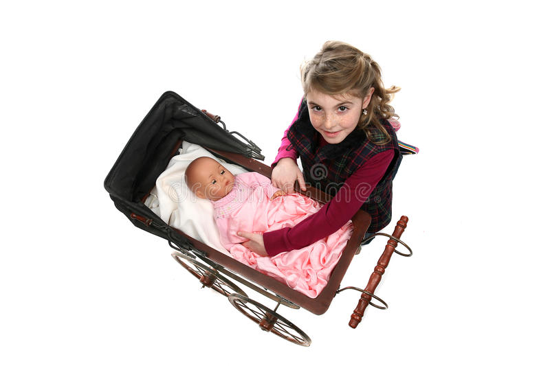 Young girl lifting doll from antique baby carriage stock image