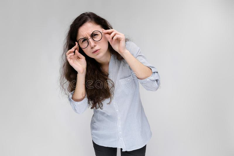 Portrait of a young girl in glasses. Beautiful young girl on a gray background. A young girl in a light blouse and dark royalty free stock photos