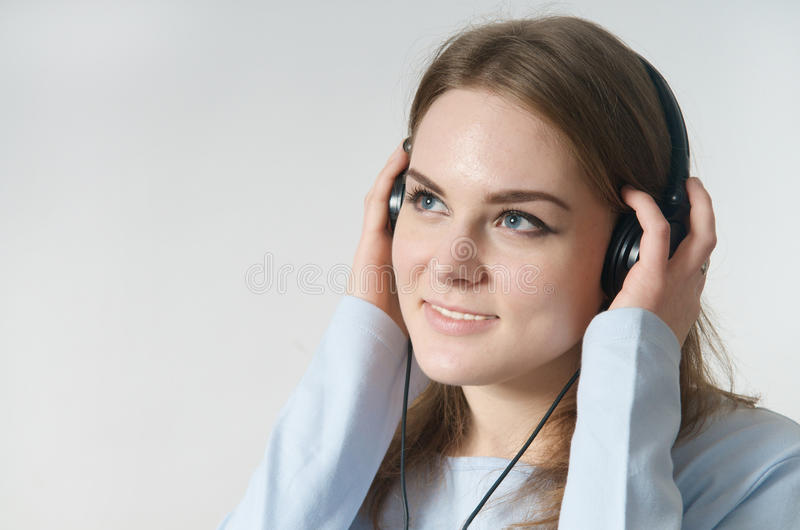 Young girl listen to music on headphone royalty free stock photos