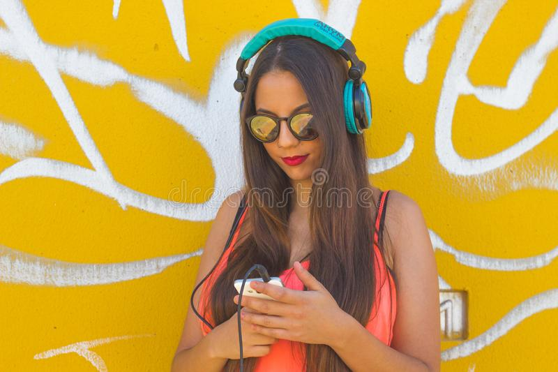 Young girl listening music in her mobile phone royalty free stock photos