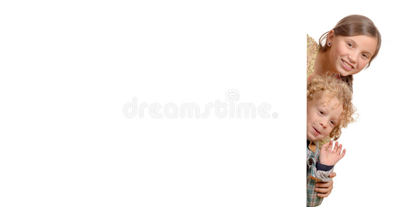 A young girl and a little boy behind a blank white poster. Isolated on white background royalty free stock photography