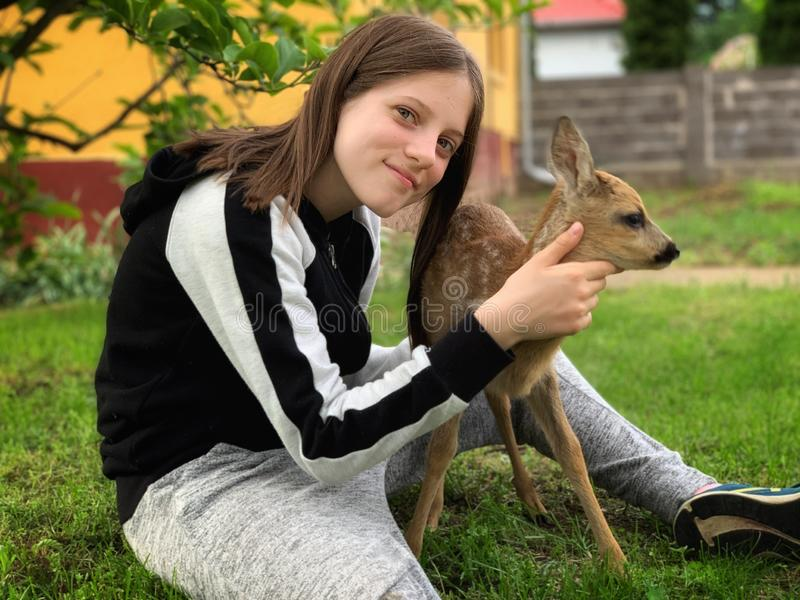 Young girl and a little deer stock photo