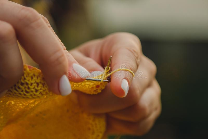 A young girl with long blond hair knits a yellow sweater in the garden in the summer. woman makes clothes with hands closeup stock image