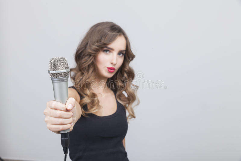 Young girl with long brown hair is giving you the microphone. Portrait of young pop star who is giving the microphone to the viewer. Concept of working with the stock image