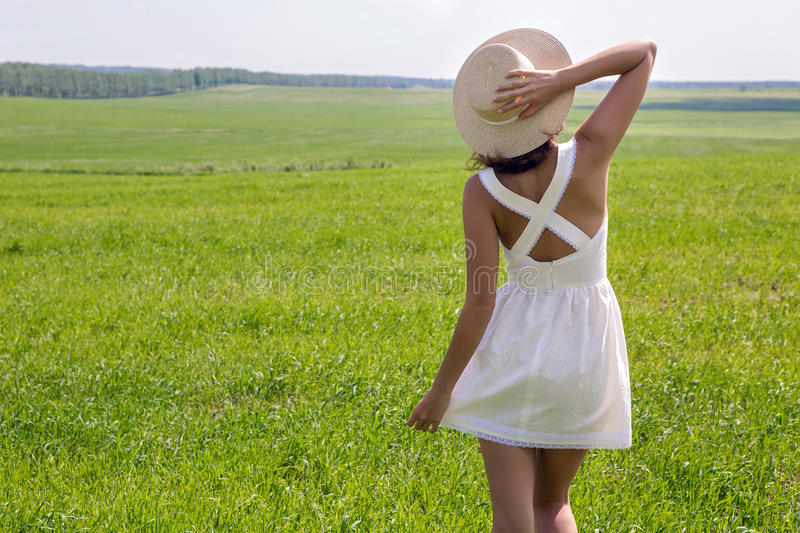 Young girl with long dark hair standing on a green field royalty free stock photo