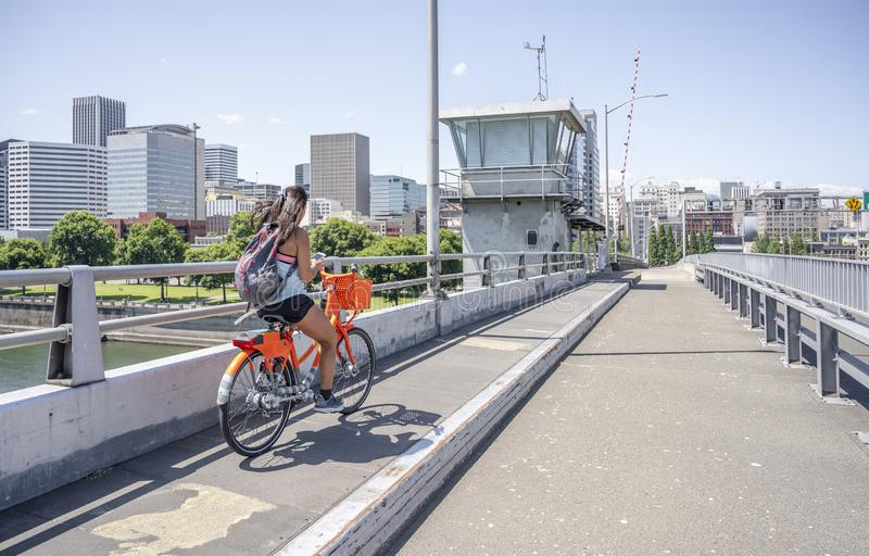 Young girl with long hair rides a bicycle on a bridge and simultaneously texting on the phone royalty free stock photography
