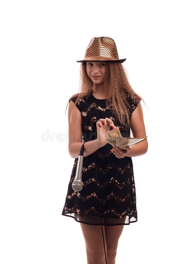 Young girl with long hair wearing a black dress and gold hat with a microphone in his hand and money on a white background in stud stock photo