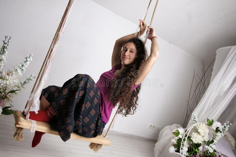 Young girl in long skirt sitting on swing in white room stock images