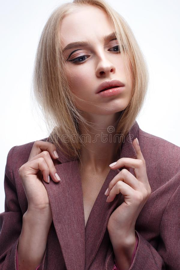 A young girl with long straight hair and nude makeup. Beautiful model in a pink coat. Blonde in a jacket. Beauty of the face. royalty free stock photo