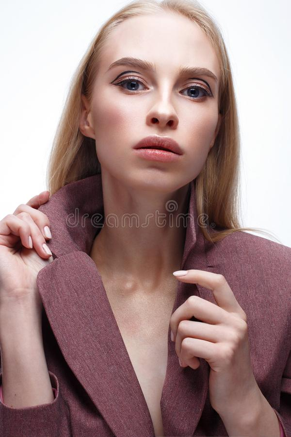 A young girl with long straight hair and nude makeup. Beautiful model in a pink coat. Blonde in a jacket. Beauty of the face. Photo is taken in the studio stock images