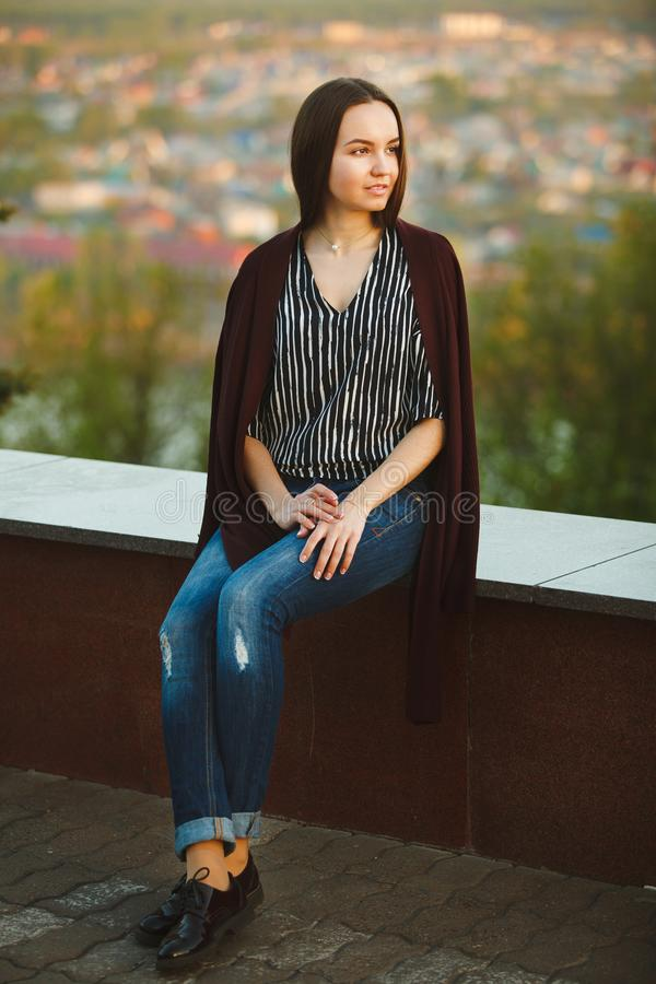Young girl in a long sweater, blouse and jeans. vertical portrait of beautiful woman. royalty free stock photos
