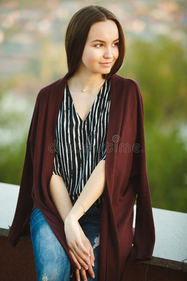 Young girl in a long sweater, blouse and jeans. vertical portrait of beautiful woman. royalty free stock image