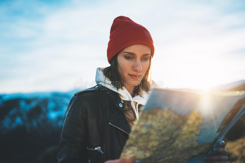 Young girl look and hold in hands map, person planning trip, hipster tourist on background sun flare nature, enjoy journey landsca royalty free stock image