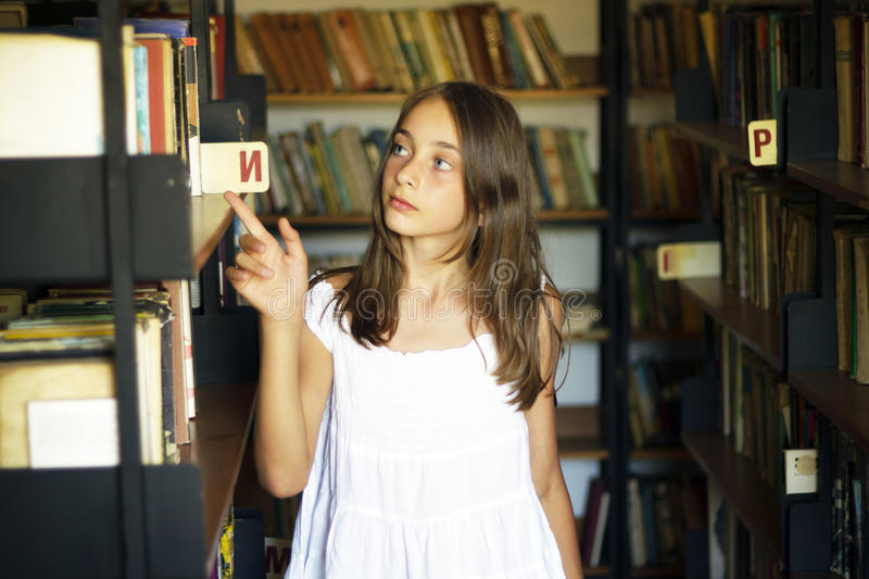 Young girl looking for a book of old library