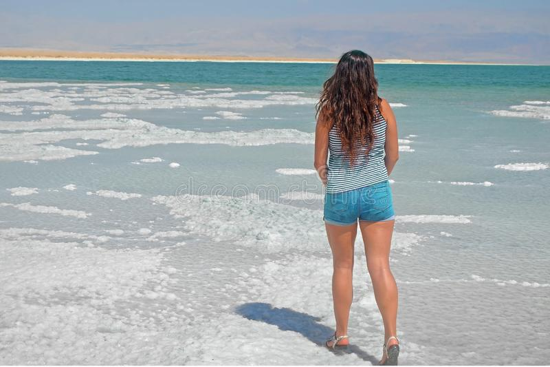 Young girl looking into the distance to the mountains. brunette walks on the islands from salt in the dead sea, Israel. stock photo
